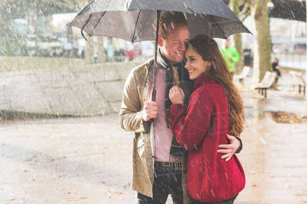 Couple with umbrella, standing under rain in park, London, UK Royalty-free stock photo