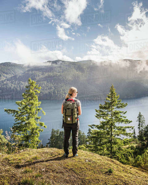 Female hiker looking out over Comox Lake, Coutenay, Vancouver Island, British Columbia, Canada Royalty-free stock photo