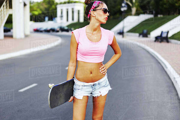 Portrait of young woman standing in street, holding skateboard Royalty-free stock photo