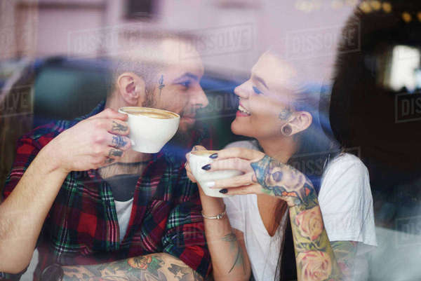 View through window of couple in coffee shop face to face smiling Royalty-free stock photo