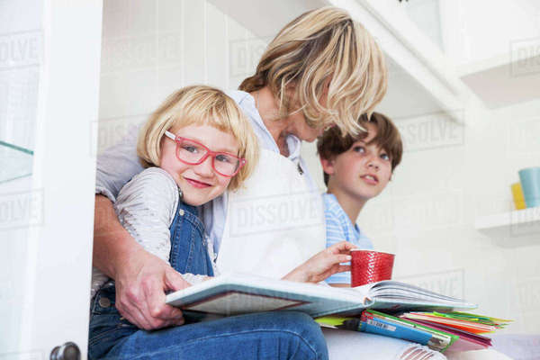 Mature woman sitting on kitchen counter reading storybooks with son and daughter Royalty-free stock photo