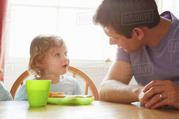 Mid adult man and toddler daughter at kitchen table Royalty-free stock photo