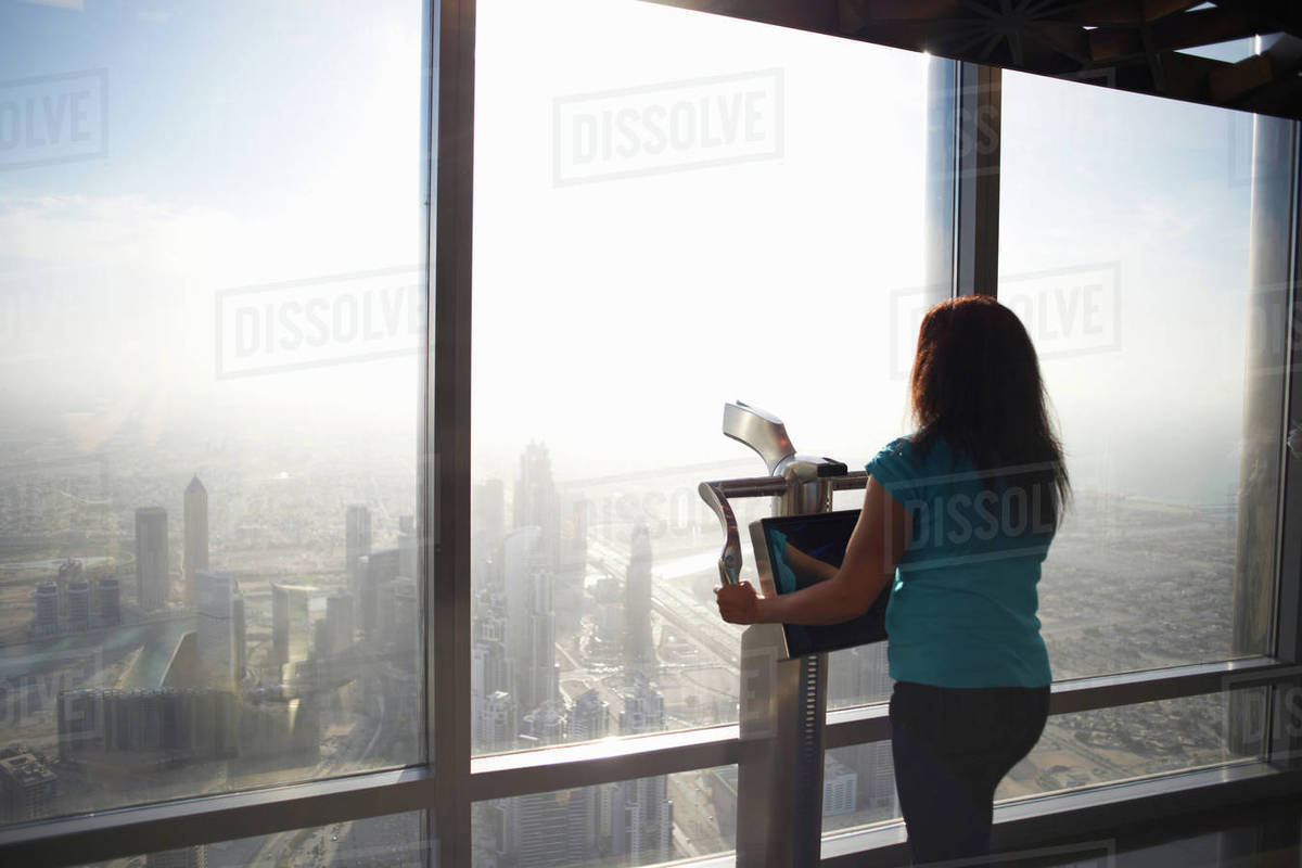 Rear View Of Female Tourist Looking Through Skyscraper Window Above