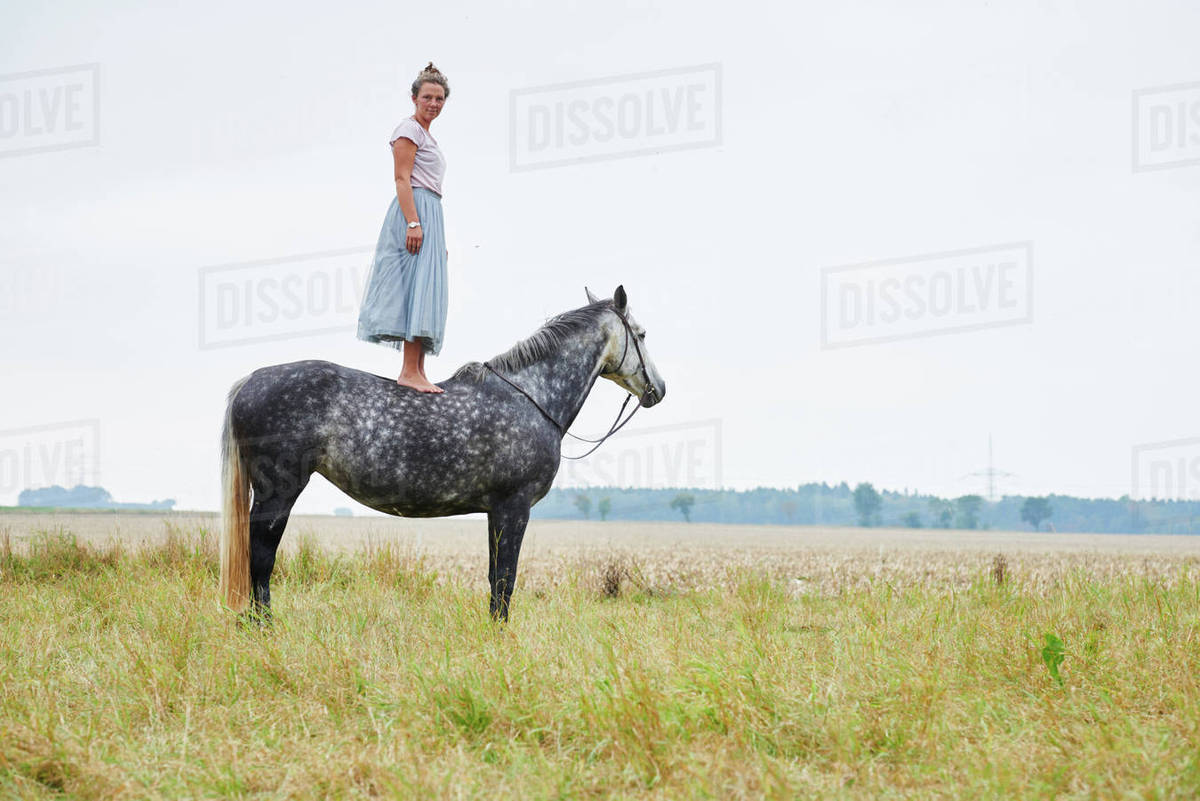 Woman In Skirt Standing On Top Of Dapple Grey Horse In Field Stock Photo Dissolve