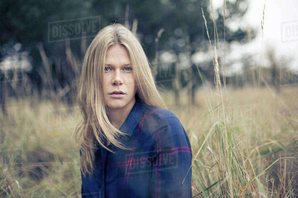Portrait of young woman with long blond hair in field of long grass Royalty-free stock photo