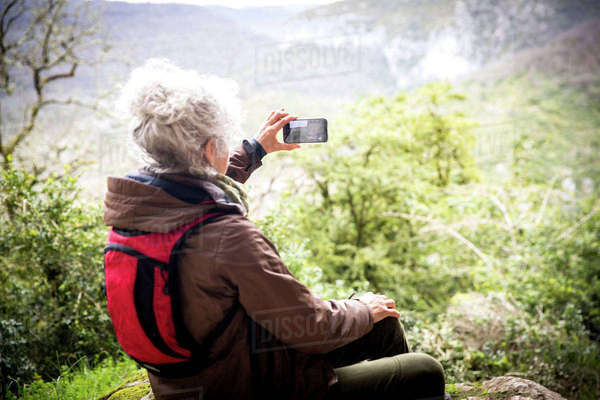 Woman hiker photographing elevated view, Bruniquel, France Royalty-free stock photo