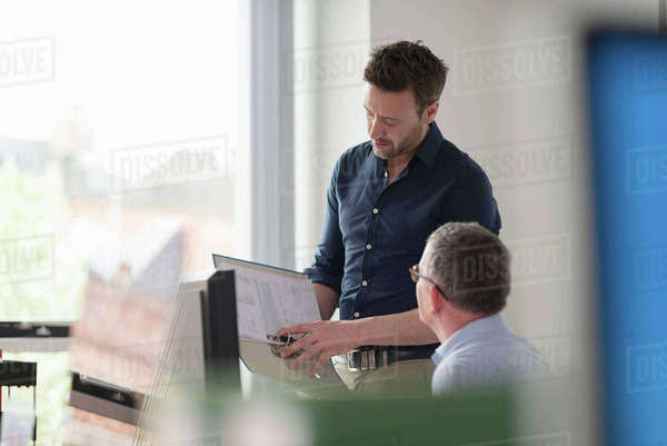 Male colleagues in discussion at office desk Royalty-free stock photo