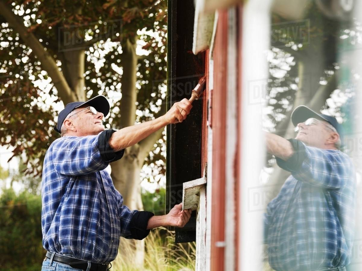 Older man painting side of house stock photo