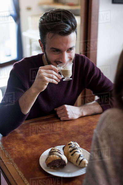Young couple sitting at table, drinking coffee, pastries on table, focus on man Royalty-free stock photo