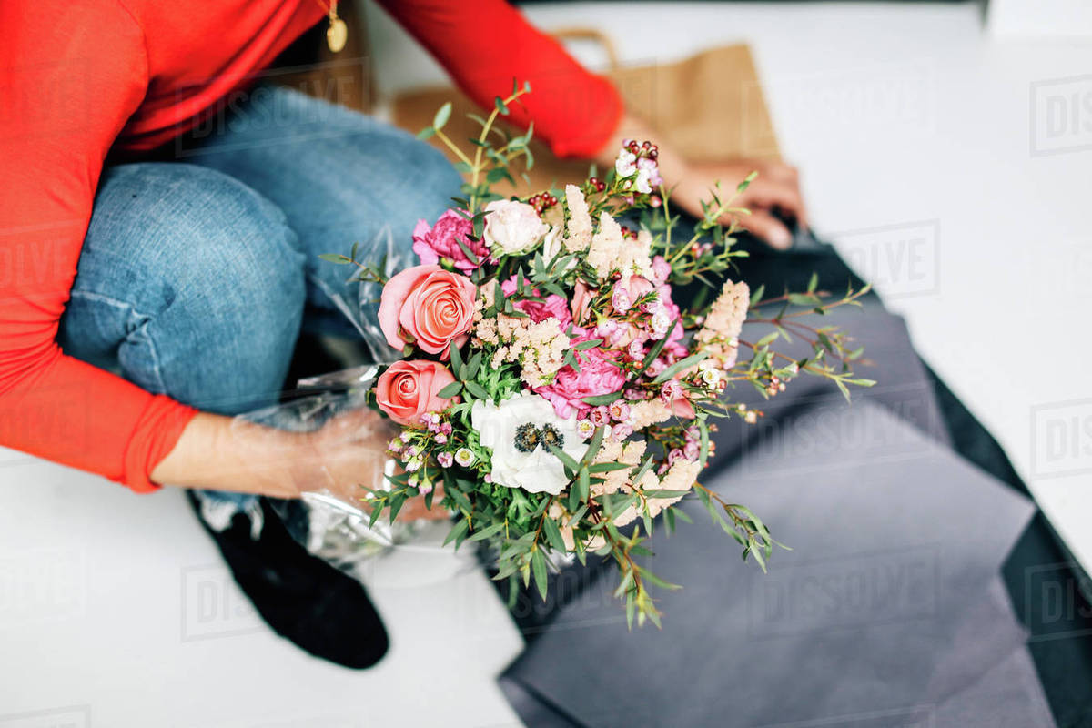 Neck Down View Of Female Florist Wrapping Flower Bouquet In Florists