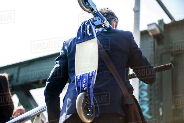 Businessman carrying scooter, Hungerford Bridge, London, UK Royalty-free stock photo