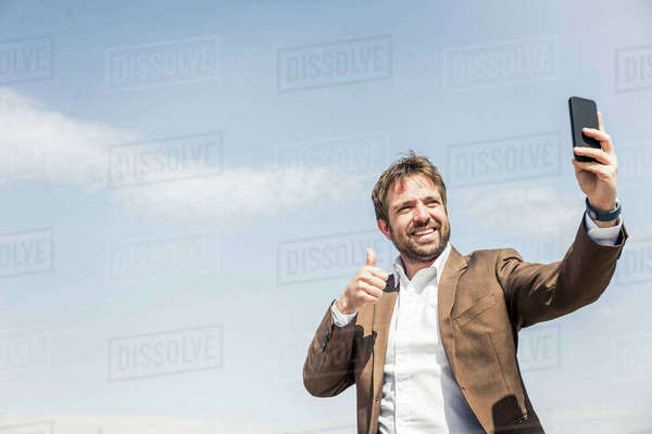 Businessman giving thumbs up for smartphone selfie against blue sky Royalty-free stock photo
