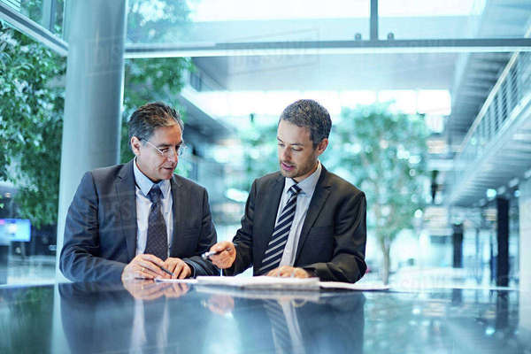Two businessmen meeting over paperwork at office desk Royalty-free stock photo