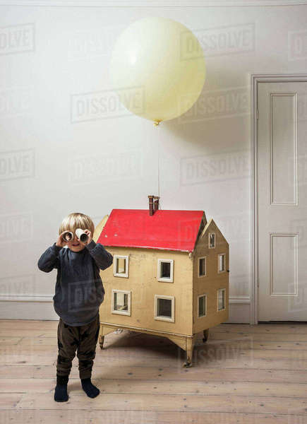 Boy standing beside dolls house looking through cardboard tube at camera Royalty-free stock photo