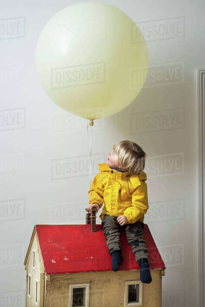 Boy sitting on dolls house looking up at balloon Royalty-free stock photo