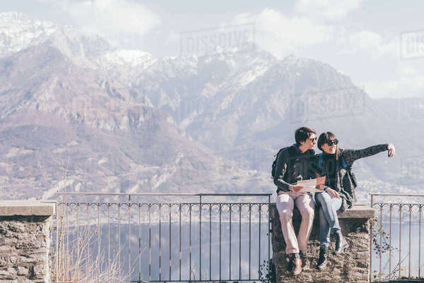 Couple sitting on terrace wall over mountain lakeside, Monte San Primo, Italy Royalty-free stock photo