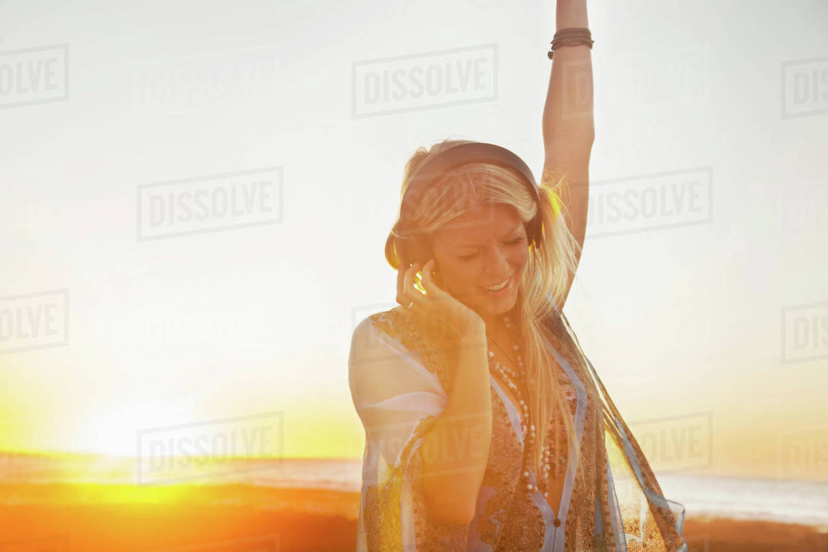 Young woman outdoors, dancing, at sunset, wearing headphones, Cape Town,  South Africa stock photo