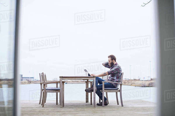 Young male designer using digital tablet on waterfront outside design studio Royalty-free stock photo