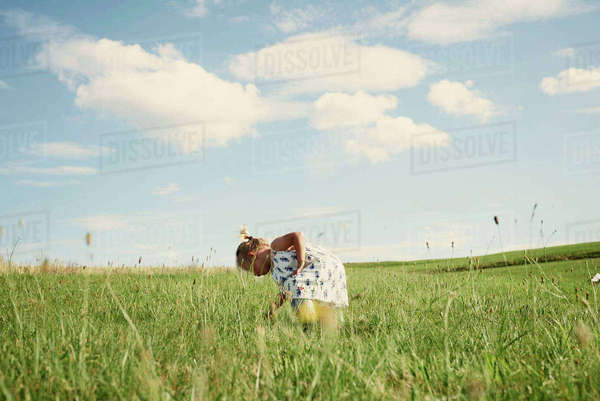 Female toddler bending forward in field picking grass Royalty-free stock photo