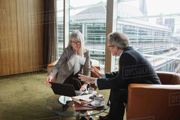 Businessman and businesswoman in coffee area in office, London, UK Royalty-free stock photo