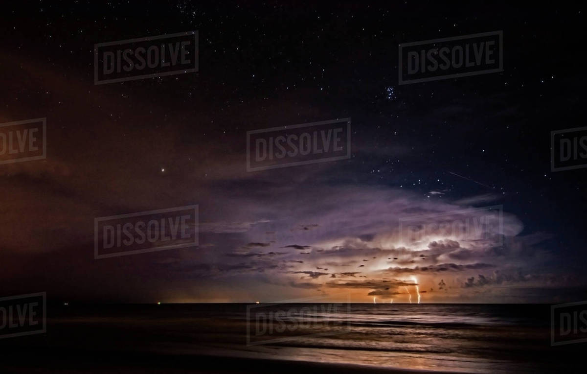 As A Lightning Storm Strikes The Atlantic Ocean Off Cocoa Beach Florida Meteor Streaks Over
