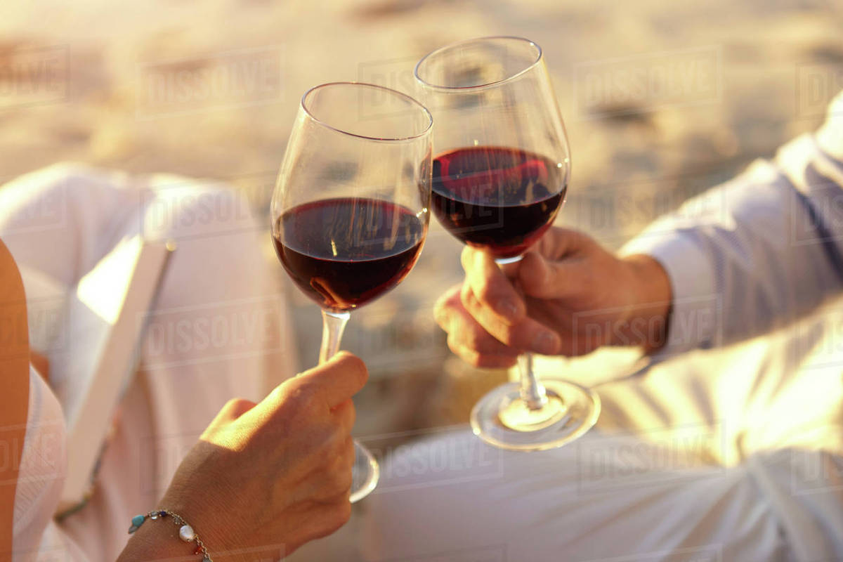 Couple drinking red wine on beach - Stock Photo - Dissolve