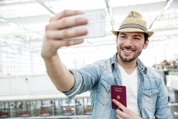 Young man holding passport taking selfie in airport departure lounge Royalty-free stock photo
