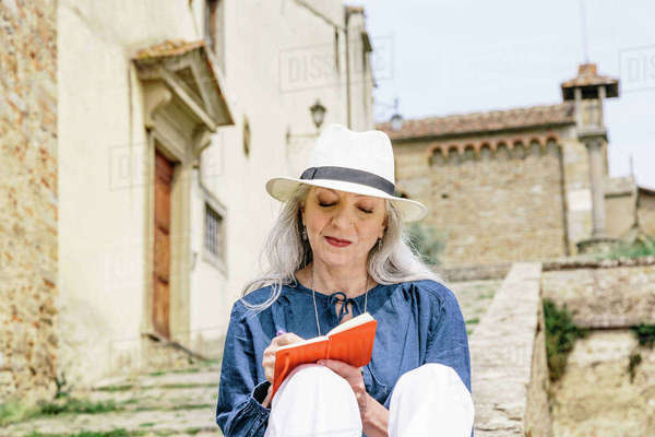 Stylish mature woman writing in notebook outside church, Fiesole, Tuscany, Italy Royalty-free stock photo