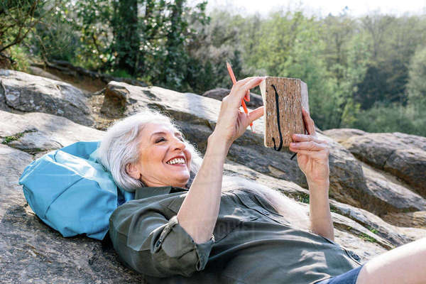 Mature female backpacker reclining on rock in forest, Scandicci, Tuscany, Italy Royalty-free stock photo