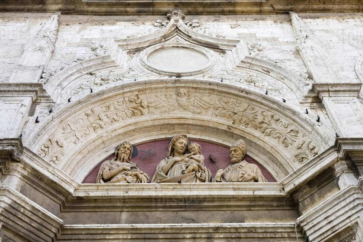 Ornate relief carvings on building wall stock photo dissolve