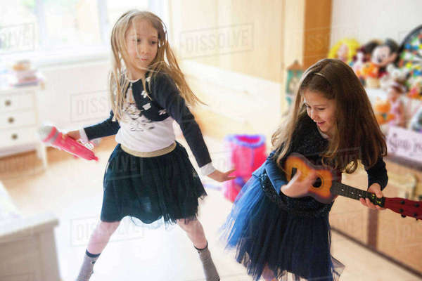 Girls singing, dancing, playing guitar Royalty-free stock photo