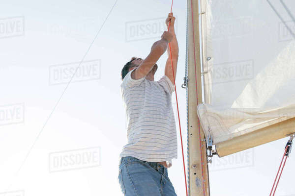 Man on sailing boat, hoisting sail Royalty-free stock photo