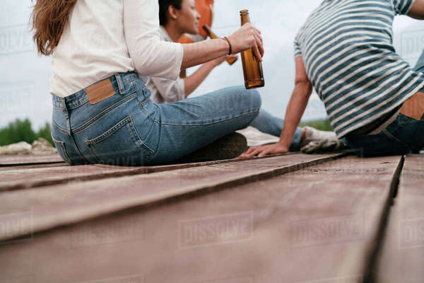 Three friends relaxing on pier, holding bottles of beer, low section Royalty-free stock photo