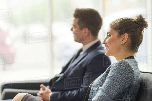 Businessman and woman sitting on sofa in office meeting Royalty-free stock photo