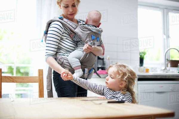 Young girl helping mother lay table, mother carrying baby boy in sling Royalty-free stock photo