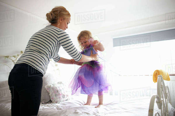 Young girl dressed in fairy costume, standing on bed, mother lifting her Royalty-free stock photo
