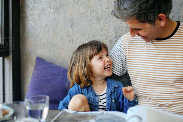 Girl laughing with father in cafe Royalty-free stock photo