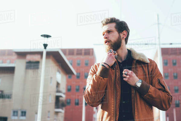 Young male hipster stroking beard on housing estate Royalty-free stock photo