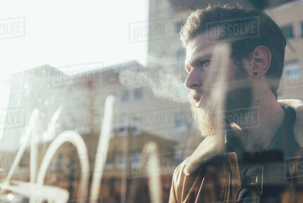 Window view of cool bearded young man at city tram station Royalty-free stock photo