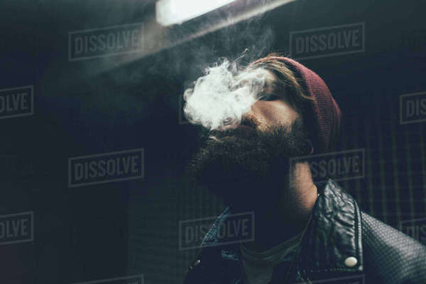 Young male hipster in knit hat smoking at night Royalty-free stock photo