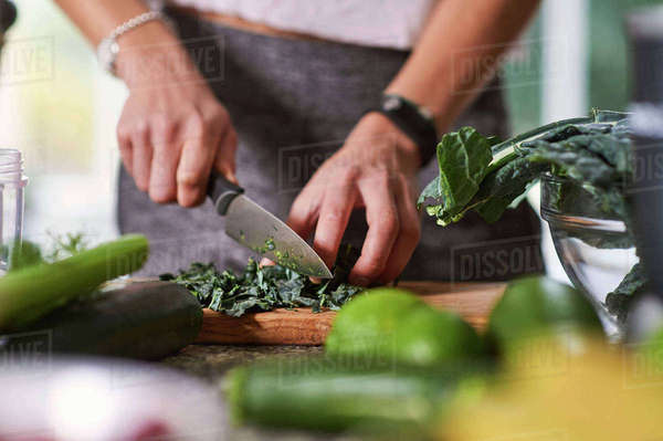 Hands of young woman slicing cabbage at kitchen table Royalty-free stock photo
