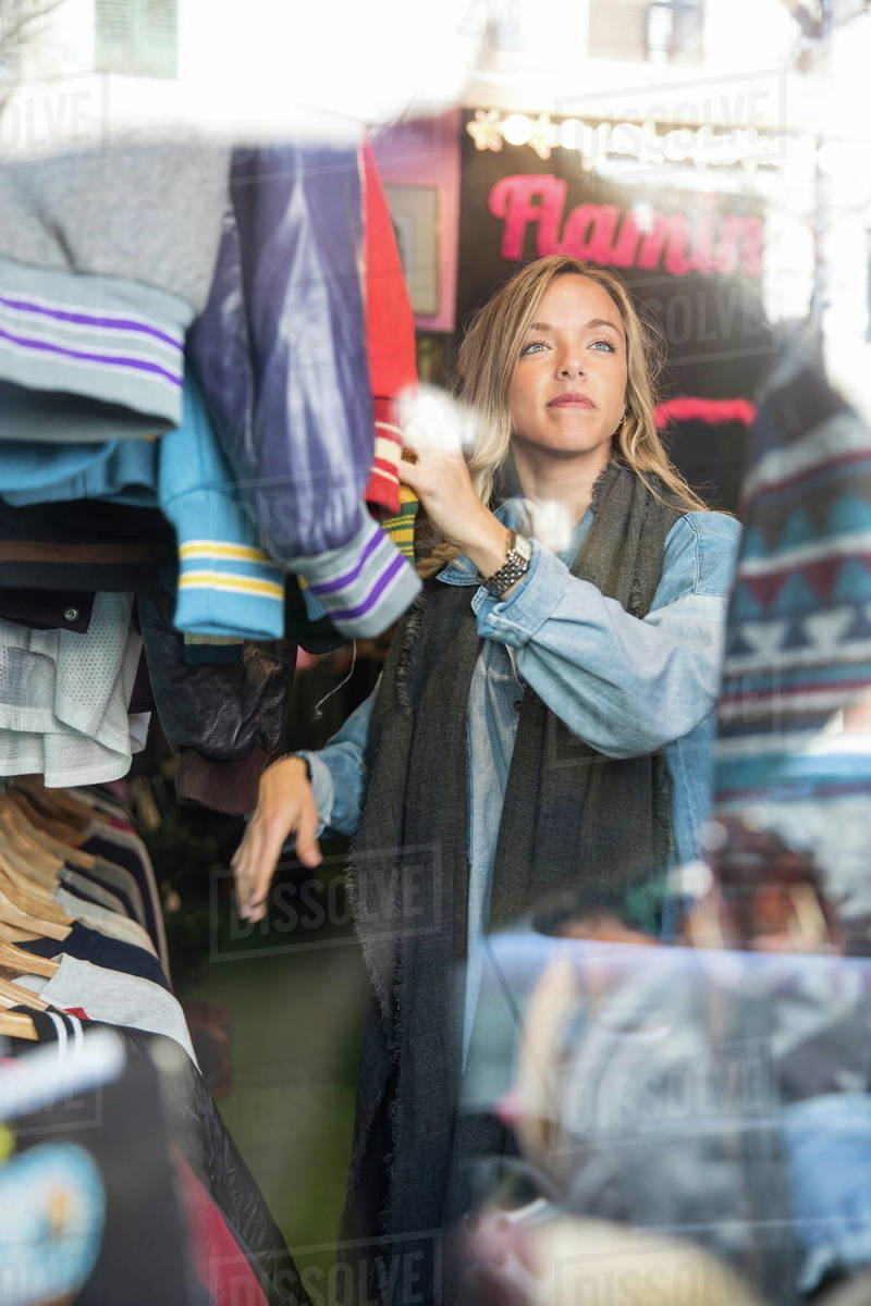 2c2b26dc2dc8d Young woman browsing vintage clothes in thrift store - Stock Photo ...