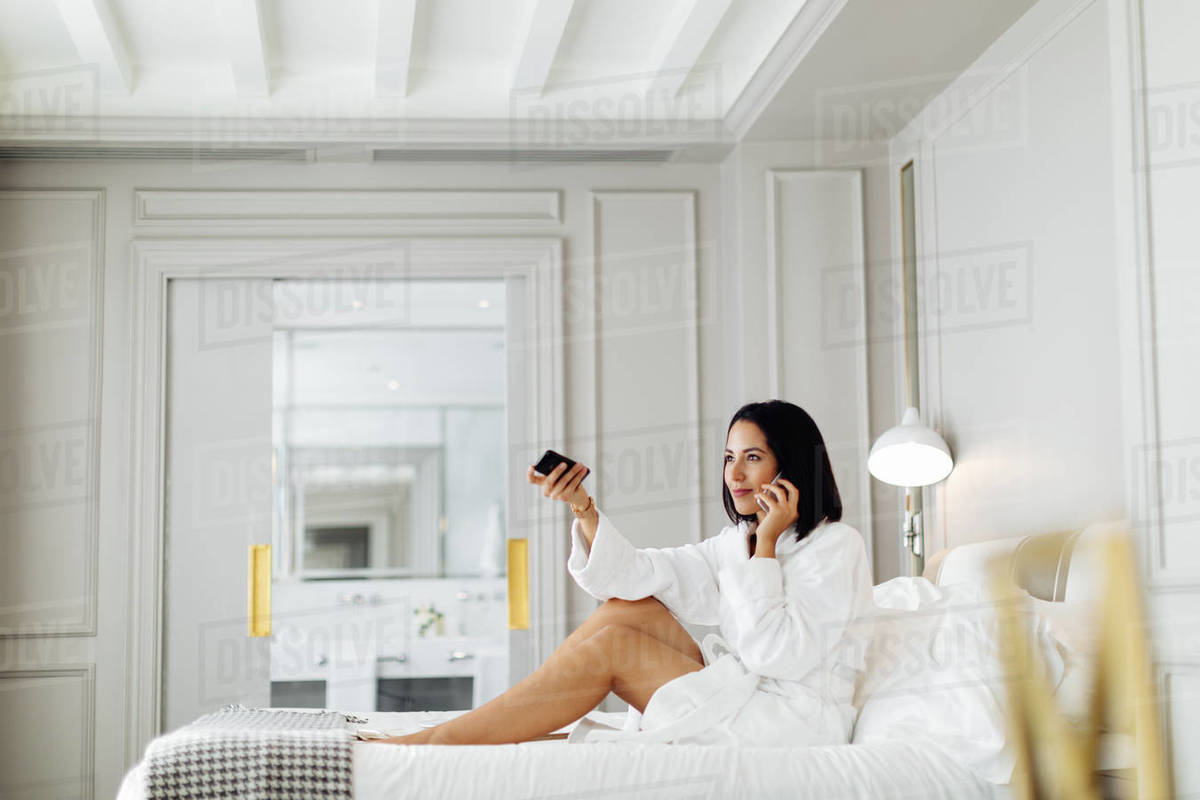 Woman using smartphone and remote control in suite Royalty-free stock photo
