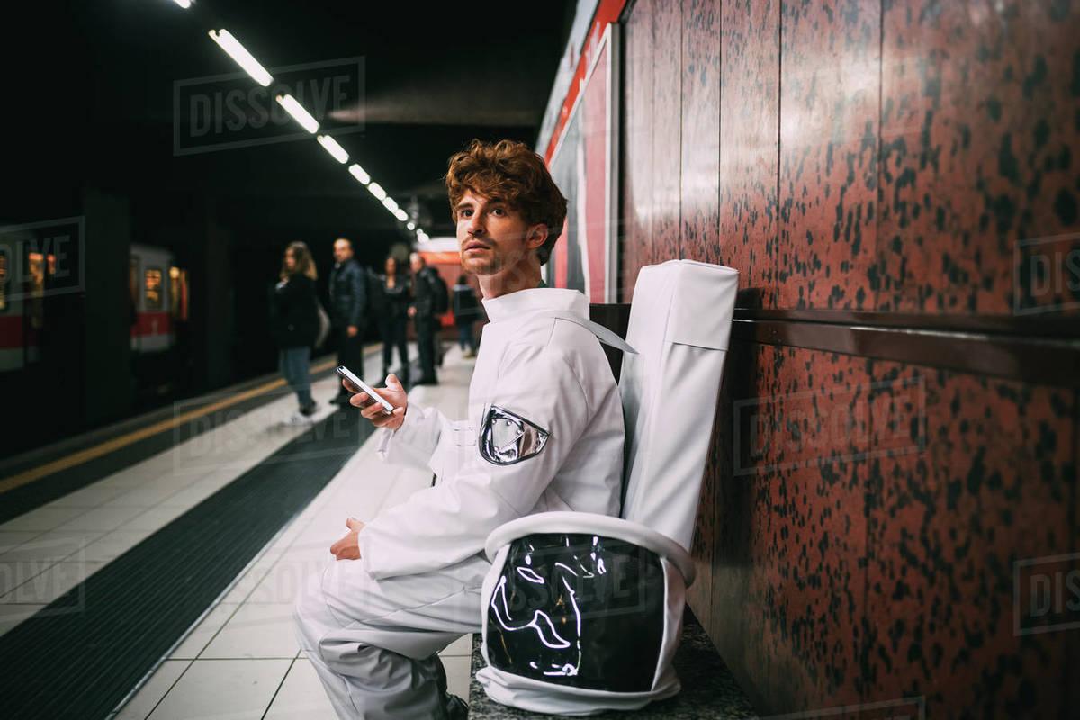 Astronaut using smartphone on train platform Royalty-free stock photo