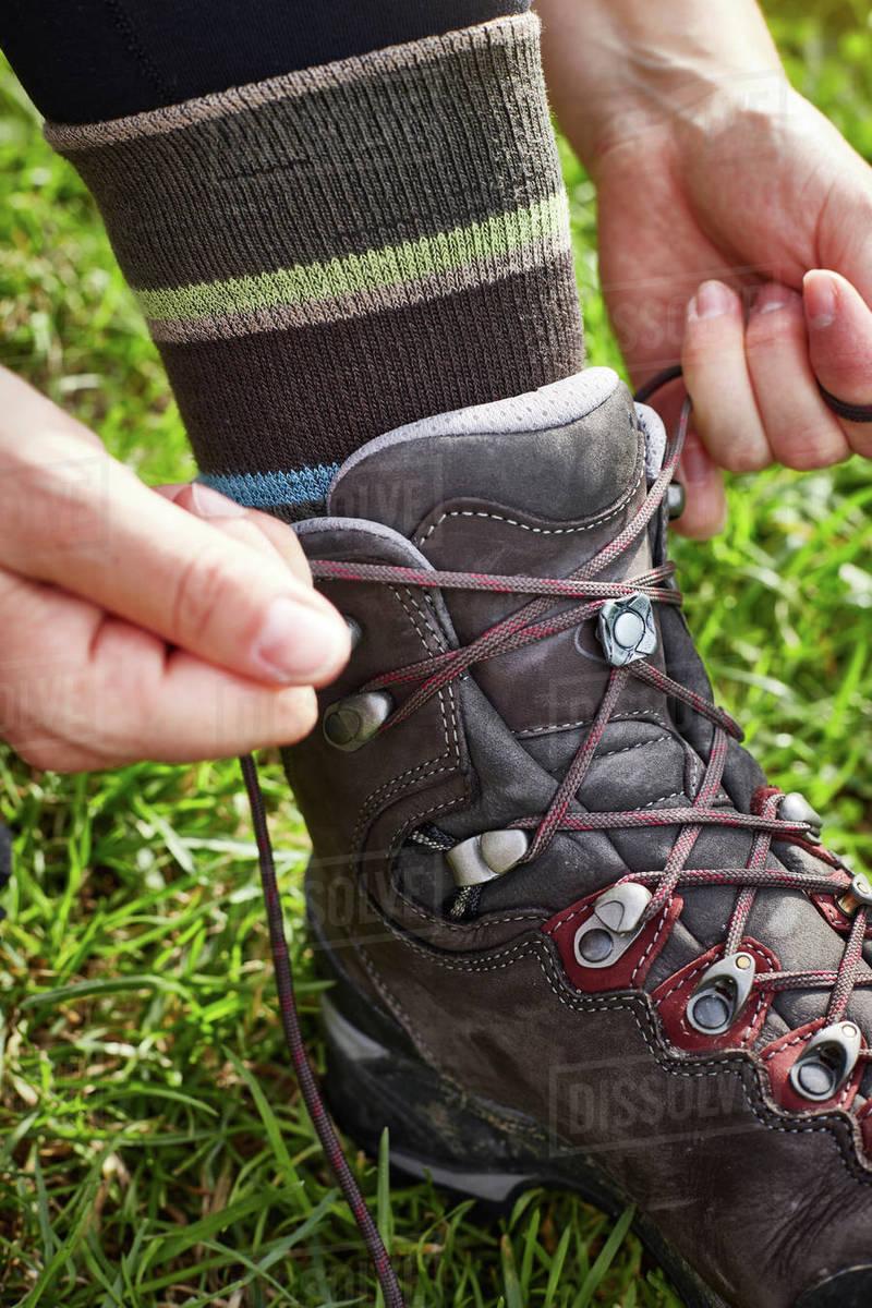 Female hiker fastening hiking boot
