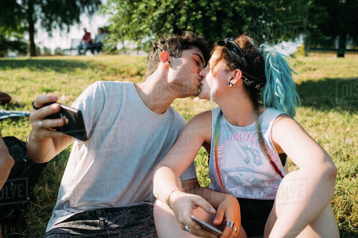 Couple kissing, using smartphone in park Royalty-free stock photo