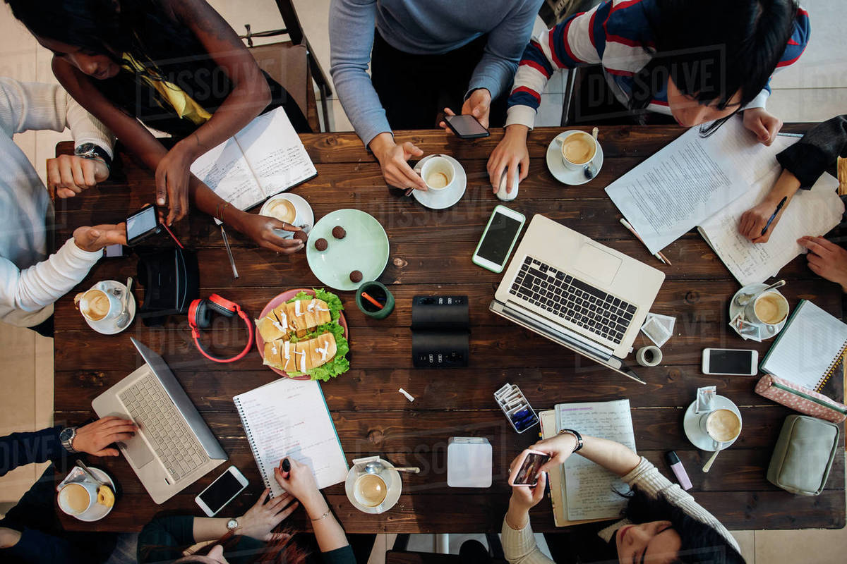 Female and male business team meeting at cafe table, overhead view Royalty-free stock photo