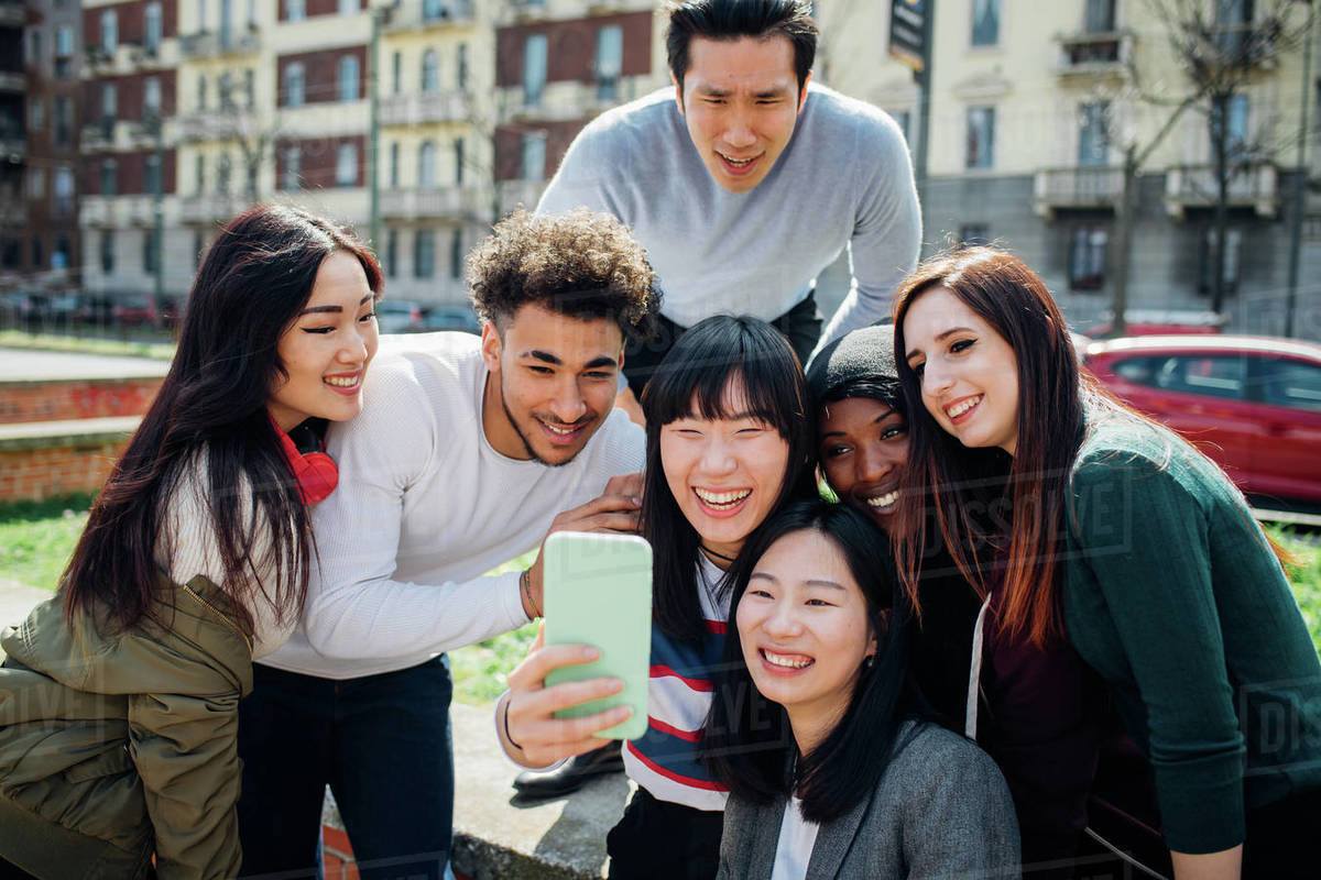 Young male and female adult friends taking smartphone selfie near city street Royalty-free stock photo