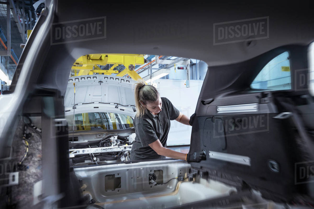 Female worker assembling car interior on production line in car factory Royalty-free stock photo