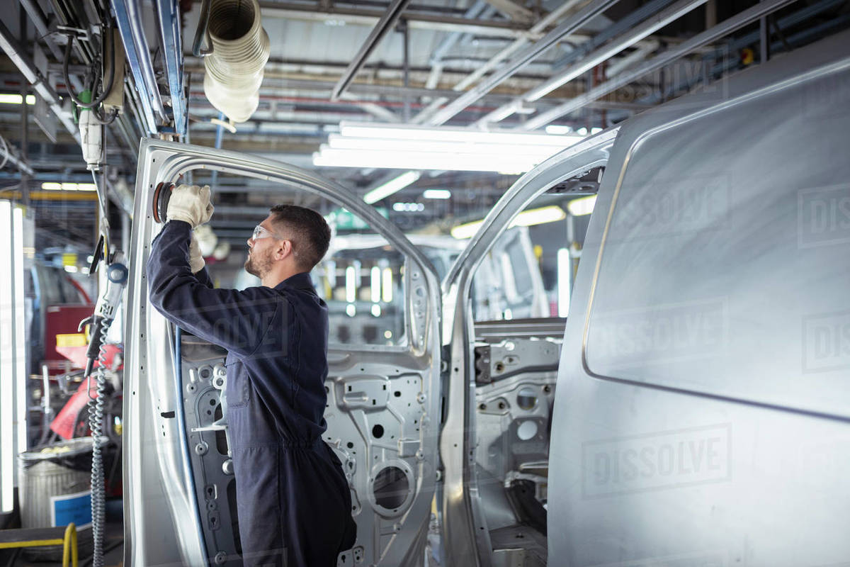 Worker sanding van body in car factory Royalty-free stock photo